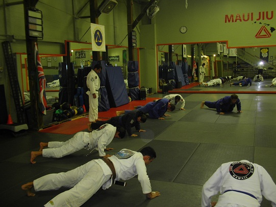 """Luis """"Limao"""" Heredia, standing as his students do push-ups."""
